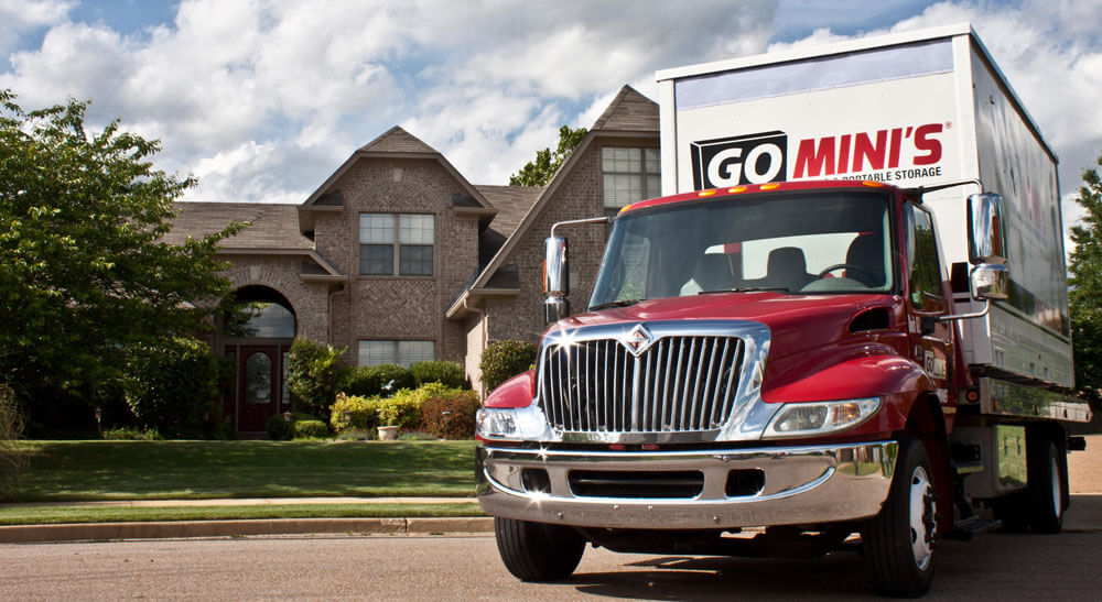 A flat-bed truck carrying a Go Mini's portable storage container parked in front of a house