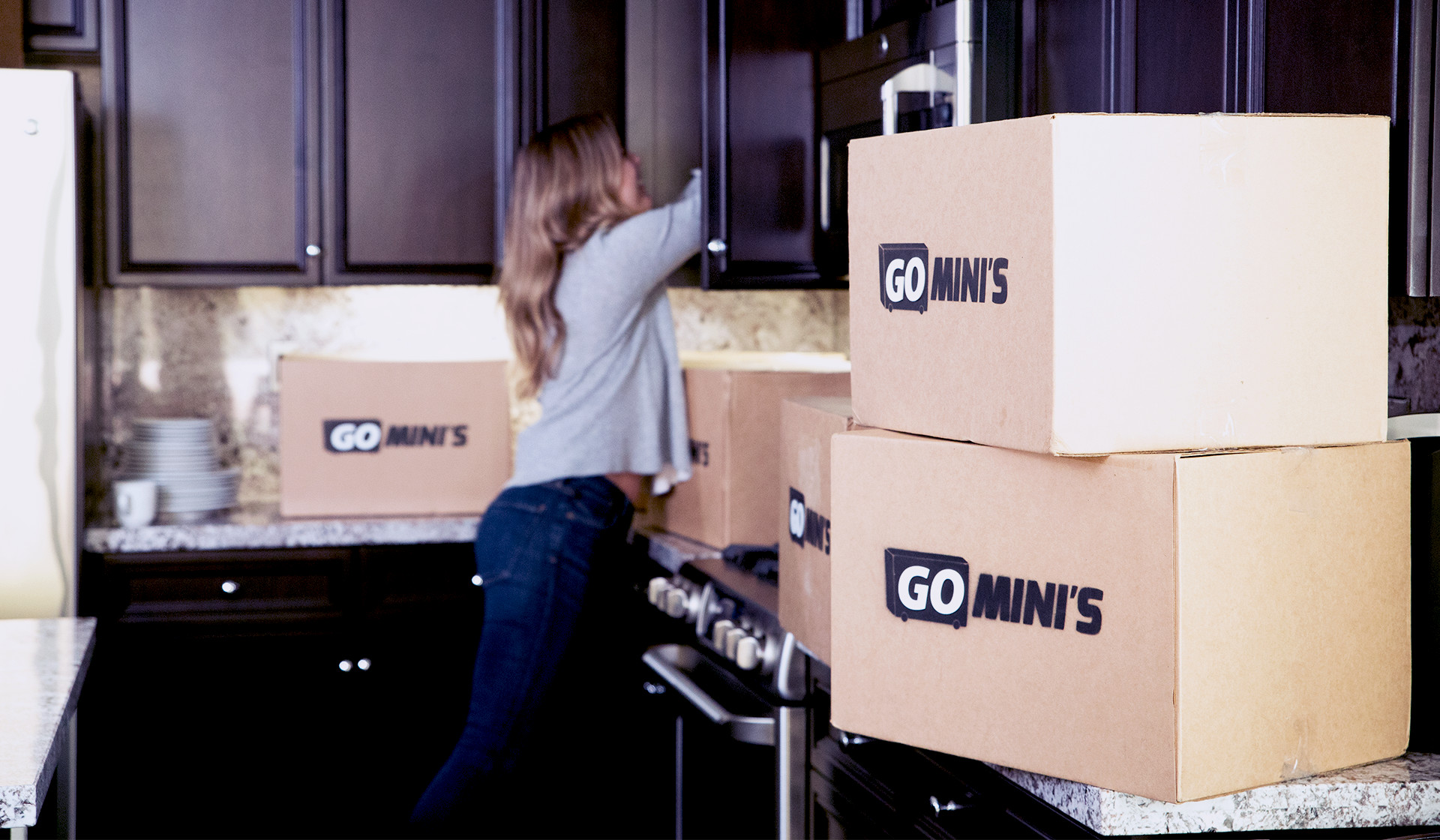 A woman reaches into a kitchen cupboard while cardboard Go Mini's moving boxes are on the counter